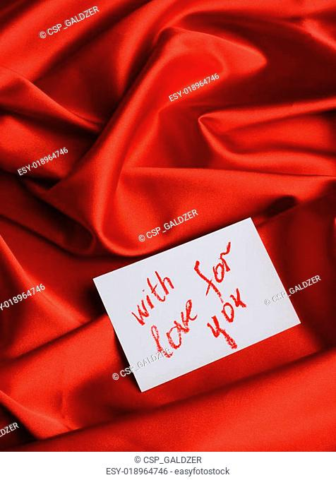 Note on red silk. With an inscription With love for you . Drawn by lipstick