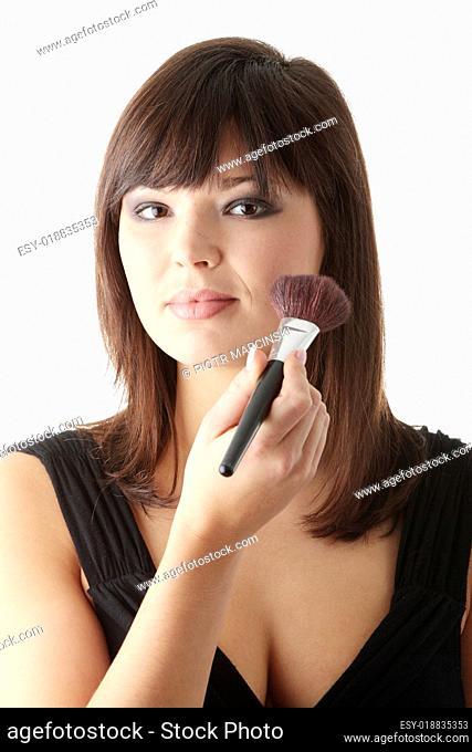 Woman in elegant black dress does a make up