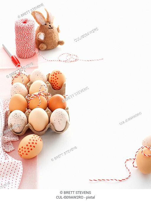 Carton of home decorated easter eggs and easter bunny on white table