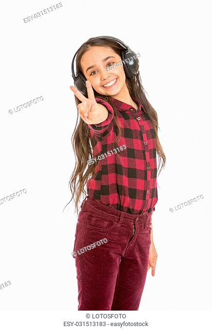 Beautiful smiling dark-haired girl in a plaid shirt and jeans listening through large black headphones music , close-up - isolated on white background