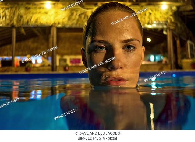 Caucasian woman floating in swimming pool at night