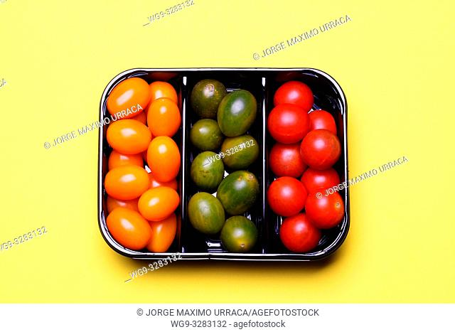 Small tomatoes whith different colors on light yellow background