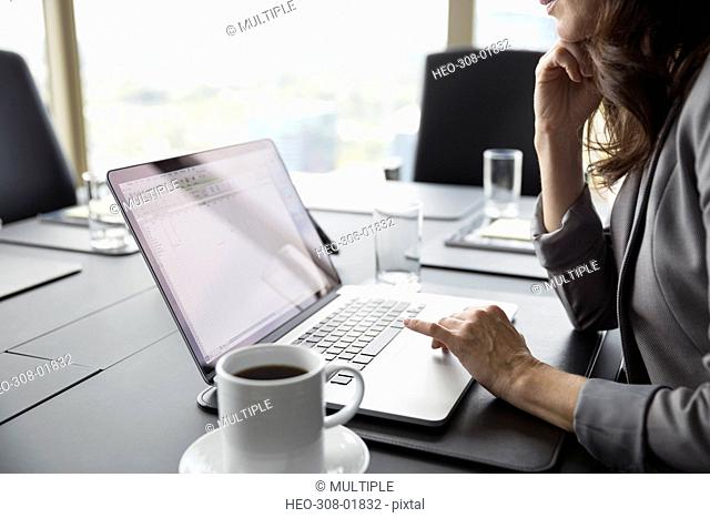 Businesswoman with coffee using laptop in conference room