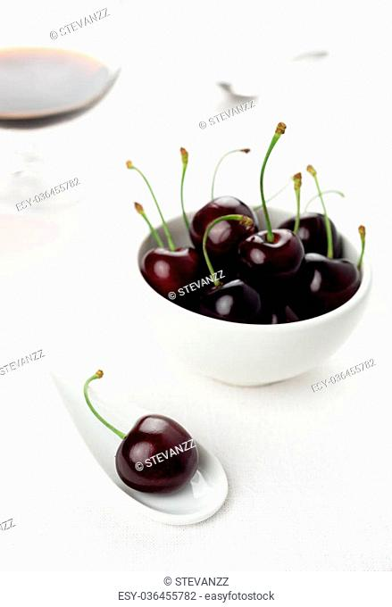 Single cherry on a white china spoon, a cherries group in a small round white bowl and a sherry glass with a spoon on background