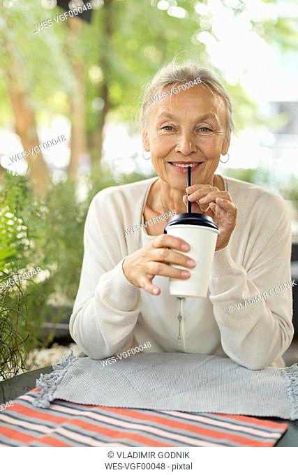 Portrait of smiling senior woman at an outdoor cafe