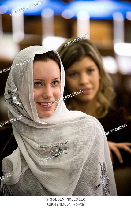 Close-up of a smiling young woman wearing a head scarf, another woman in the background