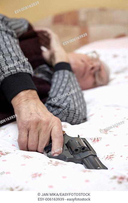 Suicide concept. Closeup of dead senior man holding a gun
