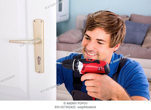 Smiling Young Carpenter Install Door Lock Using Wireless Screwdriver At Home