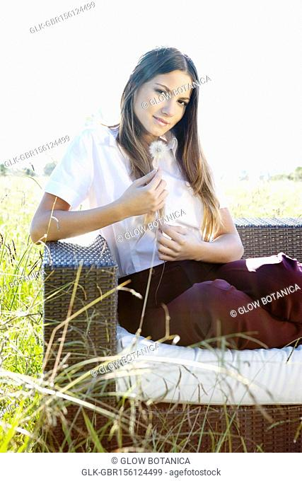 Businesswoman sitting on a sofa and holding dandelion