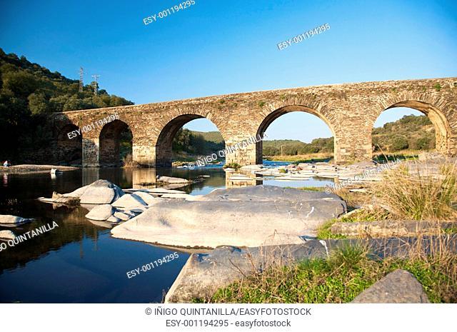 ancient stone bridge over Alagon River next to Sotoserrano village in Salamanca spain