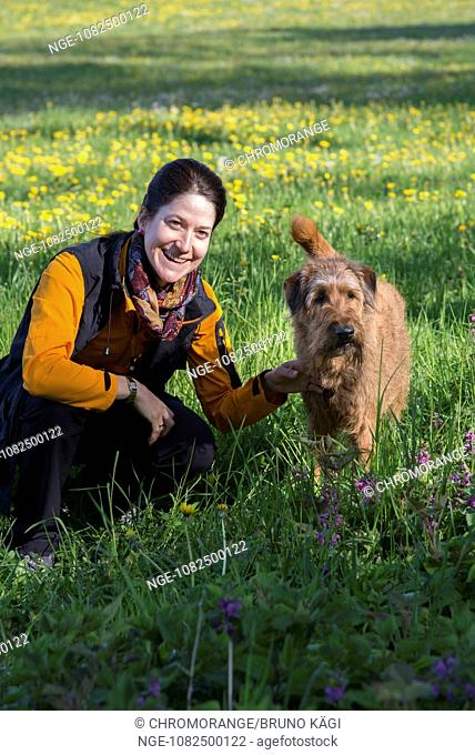 young woman and irish terrier in the meadow