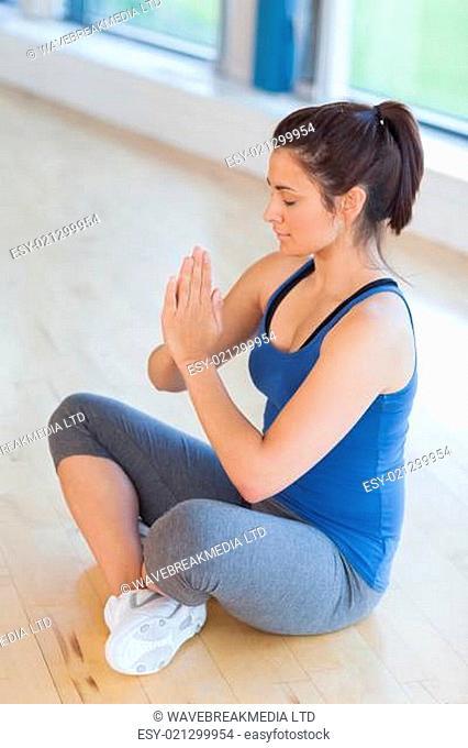Woman meditating in easy yoga pose in fitness studio