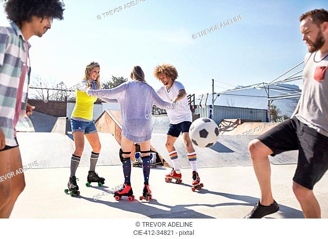 Friends roller skating and playing soccer at sunny skate park