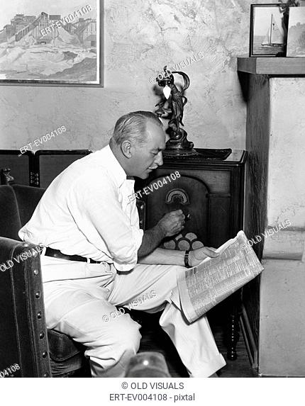 Man listening to radio and reading newspaper All persons depicted are not longer living and no estate exists Supplier warranties that there will be no model...
