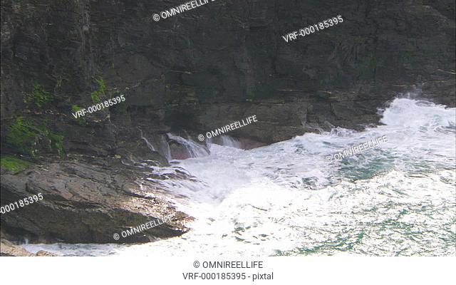 Waves breaking against rocks at base of cliffs