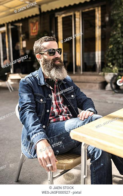 Portrait of bearded man wearing sunglasses smoking in at outdoor gastronomy