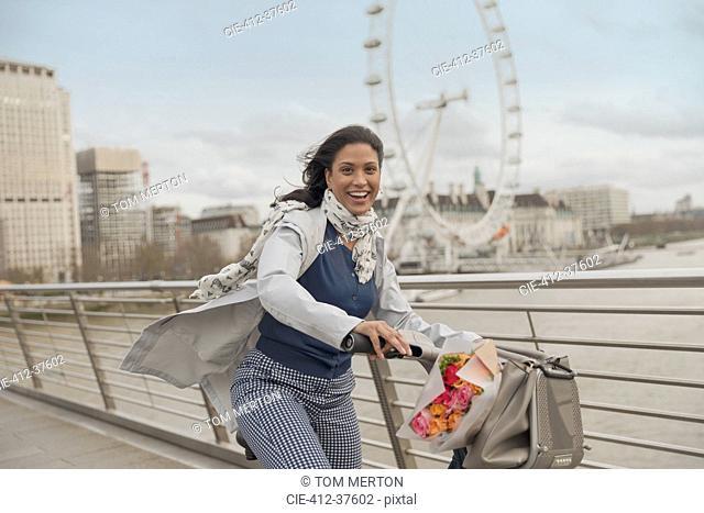 Portrait smiling woman bike riding on bridge over Thames River near Millennium Wheel, London, UK