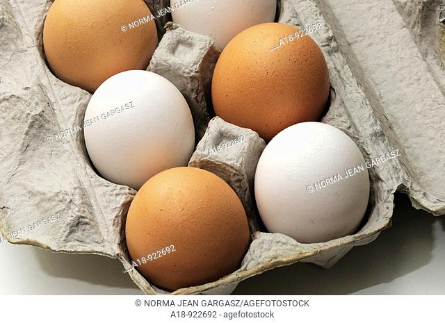 White and brown organic eggs in a paper carton