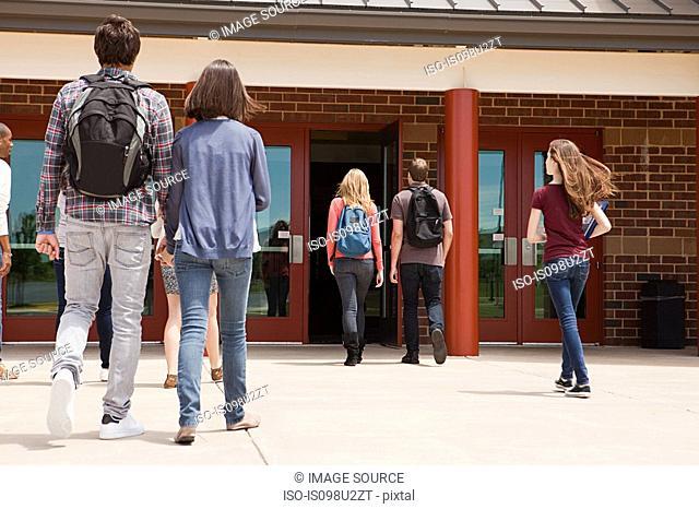 High school students entering school building