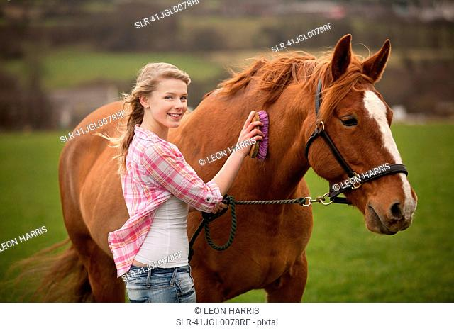 Teenage girl brushing horse in field