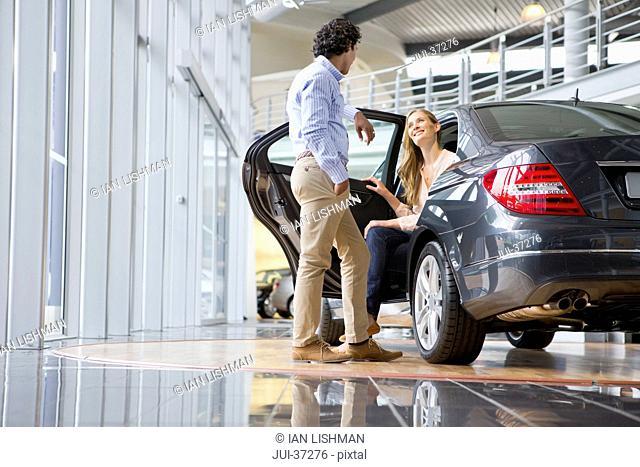 Couple looking at car in car dealership showroom