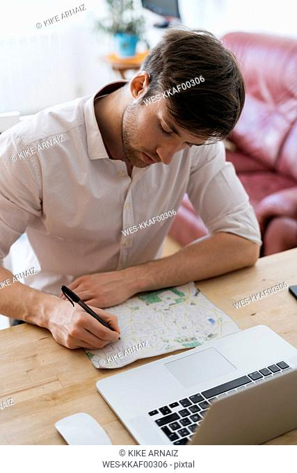 Young man with city map and laptop at home