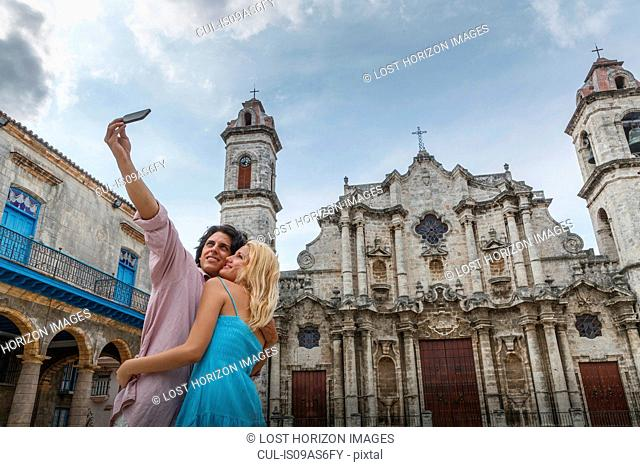 Young couple taking smartphone selfie in the Plaza de la Cathedral of Havana, Cuba