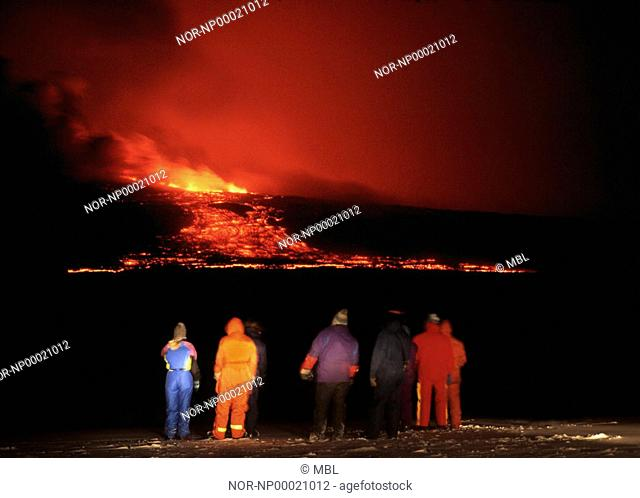 A group of people watching lava running from an eruption