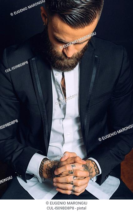 Young man wearing suit, sitting with hands clasped, tattoos on hands, pensive expression