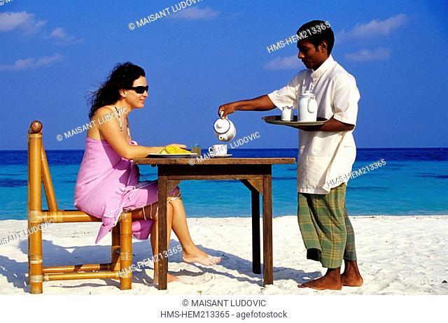 Maldives, South Ari Atoll, White Sands Resort & Spa, woman having her breakfast on the beach
