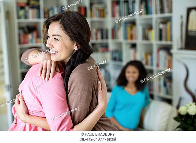 Women hugging in living room