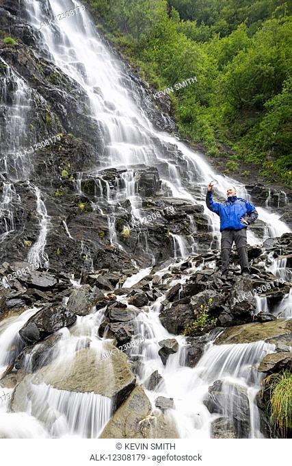 Tourist taking a selfie at Bridalveil Falls, Keystone Canyon, Valdez, Southcentral Alaska, USA