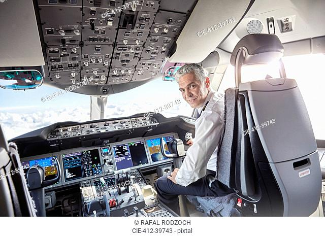 Portrait confident male pilot in airplane cockpit