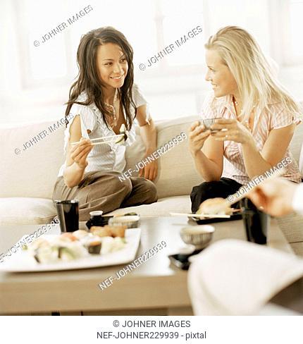 Two women eating sushi