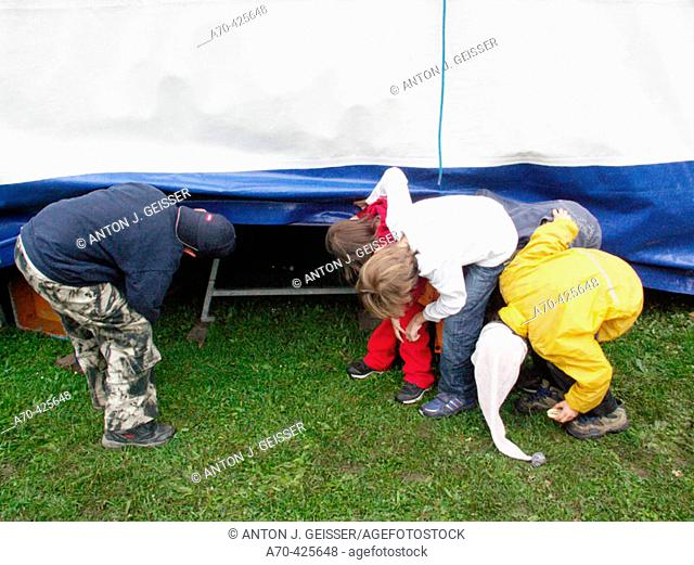 Children looking behind circus tent