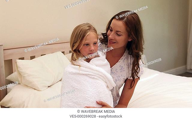 Mother sitting with her little girl wrapped up in a towel