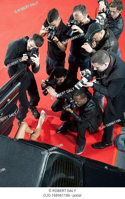 Paparazzi taking photos of celebrity's car