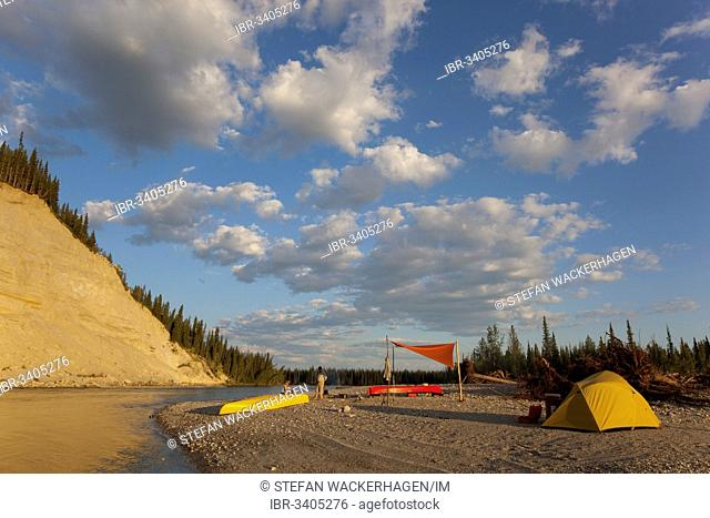 camp with tent and tarp on a gravel bar, high cut bank behind, upper Liard river, Yukon Territory, Canada