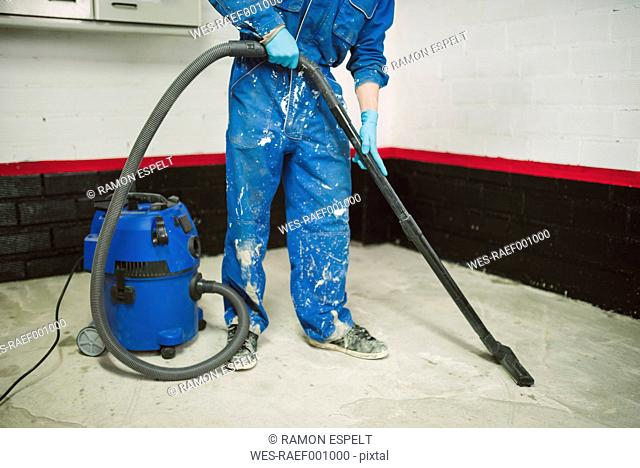 Bricklayer cleaning the floor with an industrial vacuum cleaner