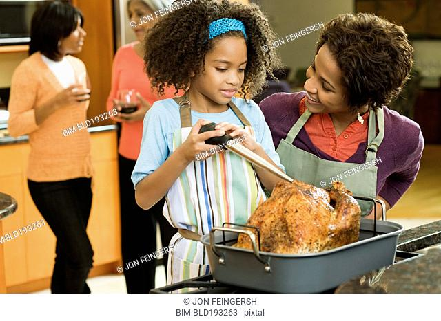 African American girl basting Thanksgiving turkey