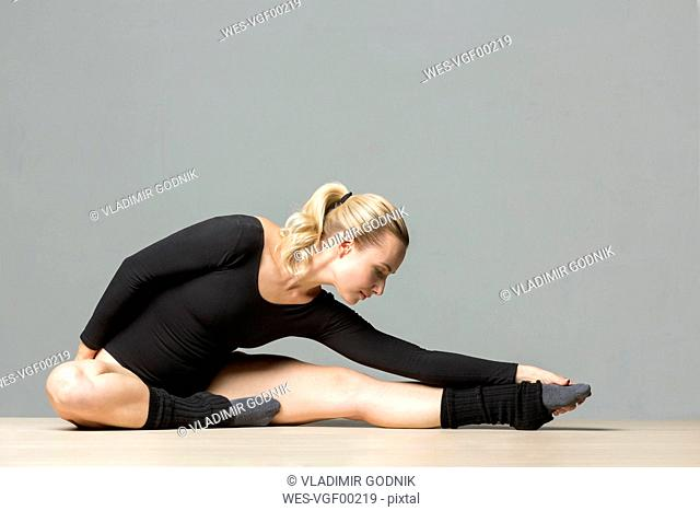 Blond woman doing stretching exercises on the floor