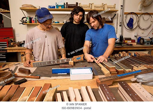 Guitar makers in workshop quality checking guitar necks