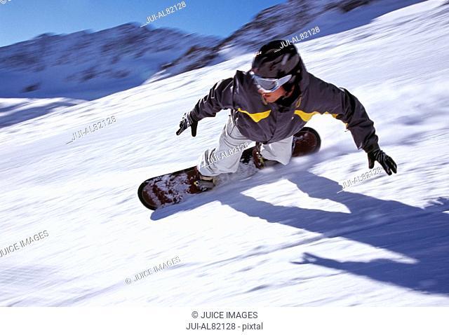 Person snowboarding down mountain