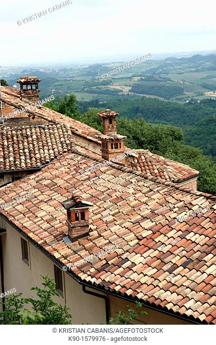 Traditional red pantiles of the roofs of residential houses of a small village in Piemont, with chimneys and view across the adjencent green landscape, Italy