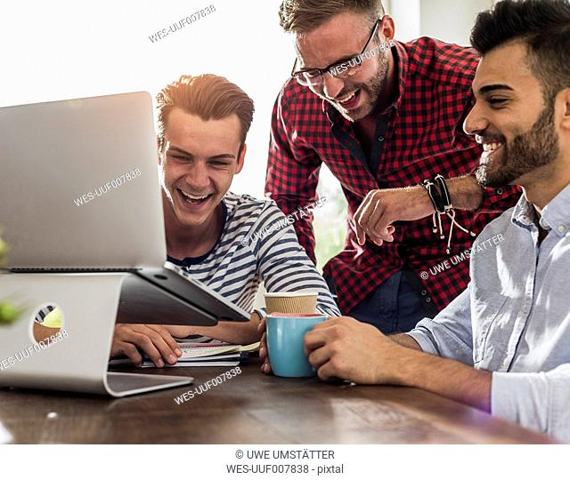 Three happy young professionals sharing laptop in office