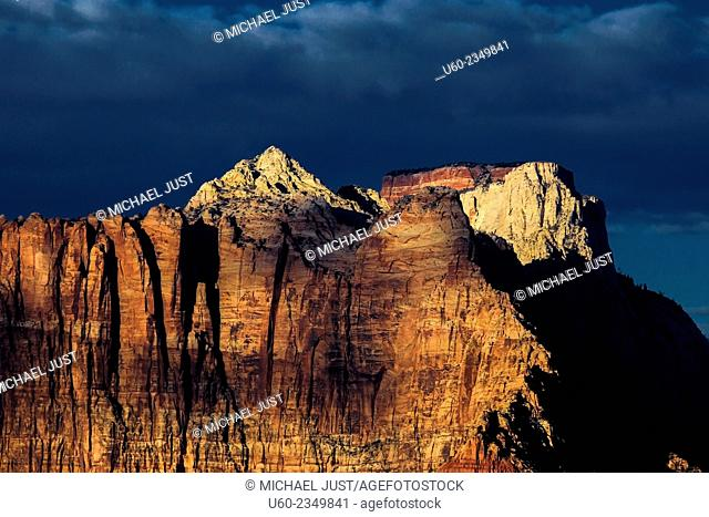 The setting sun shines on the West Temple at Zion National Park as seen from Gooseberry Mesa, Utah