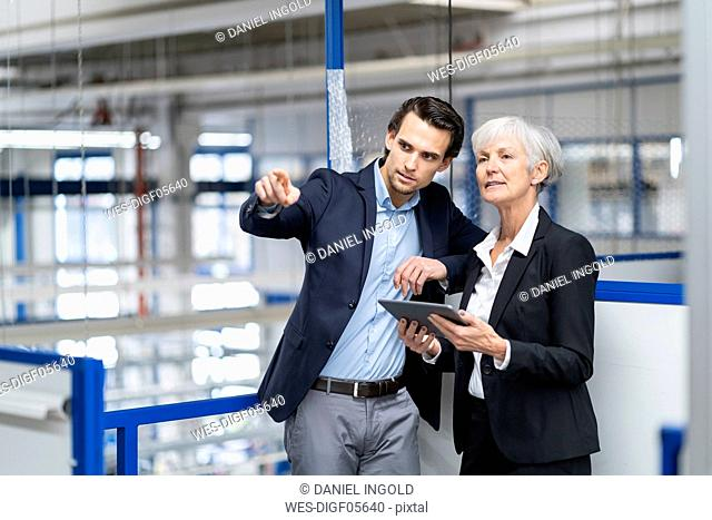 Businessman and senior businesswoman with tablet talking in a factory