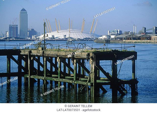 View of Canary Wharf tower and white roof of Millennium Dome. Wooden jetty in water. River Thames