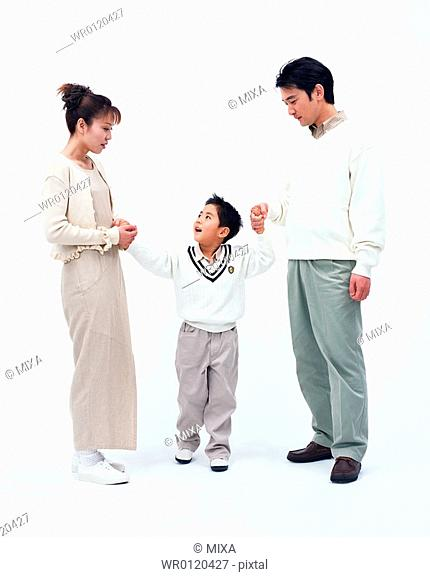 A boy holding hands with his parents