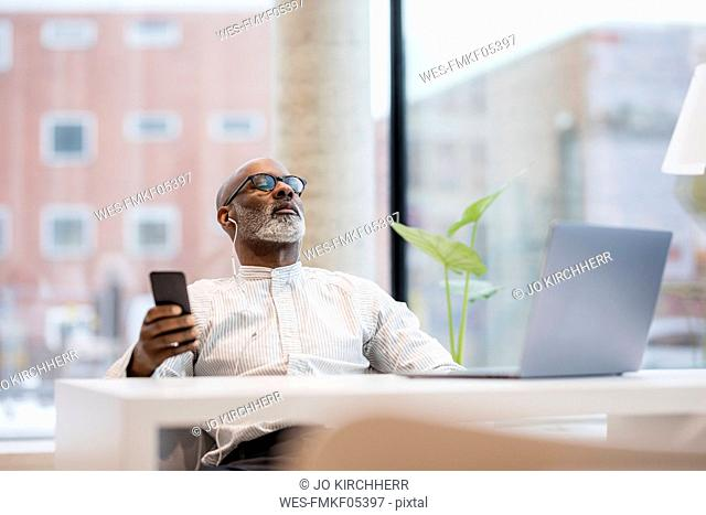 Mature businessman listening music with smartphone and earphones relaxing